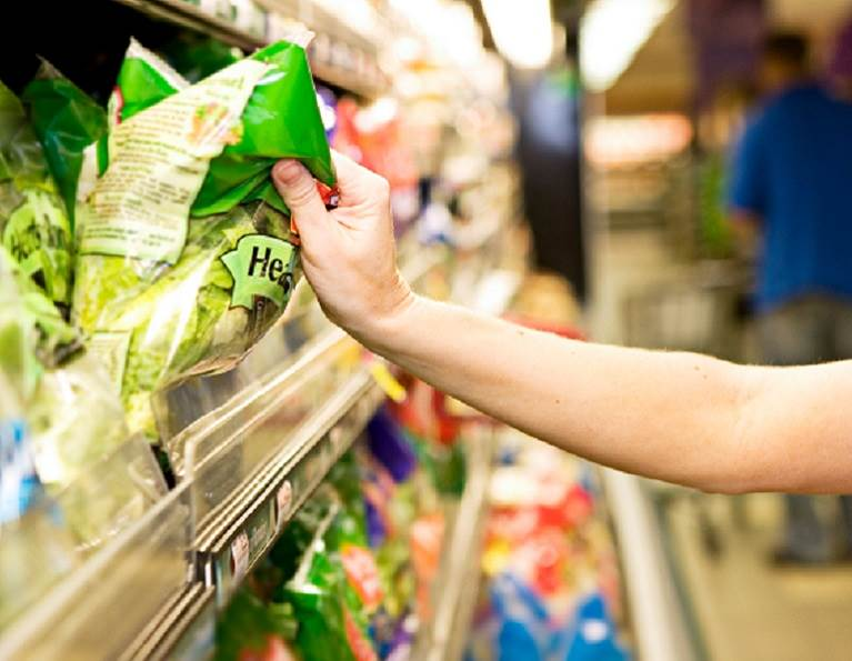 Someone grabbing a lettuce bag in a grocery store manufactured with flexible packaging adhesives.